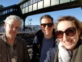 Seamus, Paul and Anna standing on a balcony overlooking rail tracks and the Hudson River. It is a sunny day.