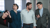 Four people standing in a white room, looking perplexed.